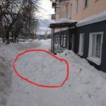 У центрального входа в детско-юнощескую библиотеку сугроб на тротуаре. Этот снег упал с крыши.