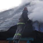 Пожарный тушит горящую крышу