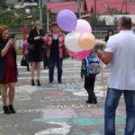Дети и родители пришли в школу с цветами и воздушными шарами