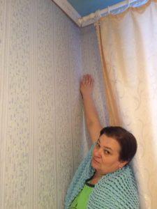 Женщина показывает, что в этом углу промерзают стены