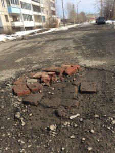 А это участок дороги по переулку Школьному. Потеряв надежду на ремонт, местные жители своими силами пытаются бороться с глубокими ямами.
