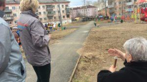 Местная жительница показывает, какие недочеты есть на площадке.